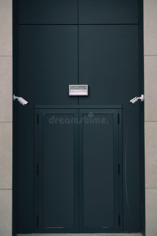 Entrada oscura cerrada de la puerta del club nocturno o de la discoteca con la cámara de seguridad foto de archivo