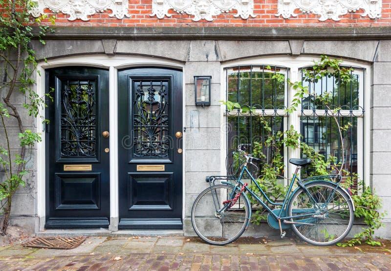 Entrada típica da casa com duas portas e bicicleta em Amsterdão fotografia de stock royalty free