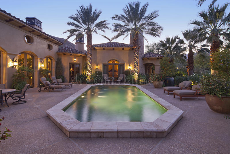 Entrada traseira da casa de campo luxuosa na noite com piscina imagem de stock