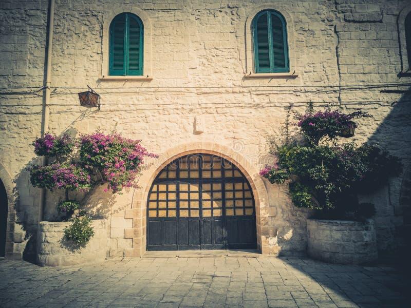 Entrada a una casa antigua con la puerta arqueada, las ventanas y las flores ornamentales foto de archivo