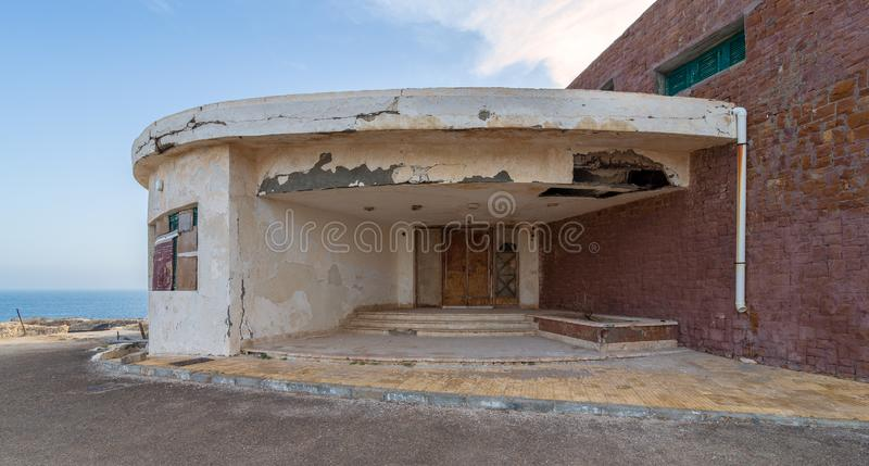 Entrance of abandoned old house by the sea with grunge weathered wooden double leaves door and brown stone bricks royalty free stock image