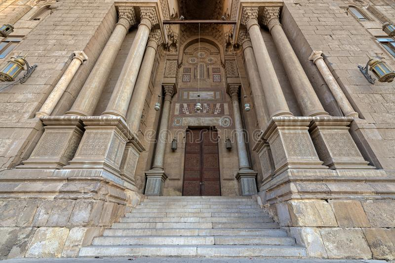 Entrance of al Rifai Mosque with closed decorated wooden doors, ornate columns, stone wall and stairs, Old Cairo, Egypt. Entrance of al Rifai Mosque with closed stock image