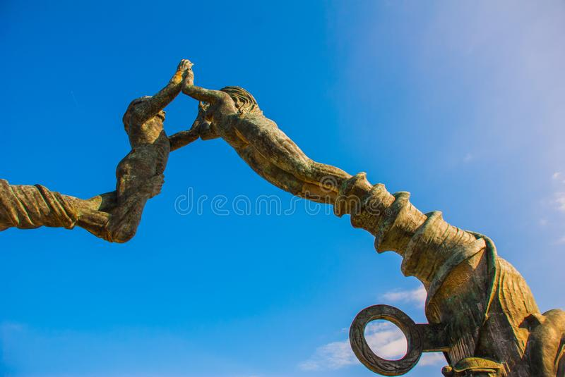 Entrance of the beach in Playa del Carmen, Mexico. Riviera Maya. Sculpture of a man and woman`s joined hands.  royalty free stock photography