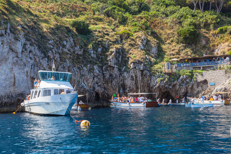 Entrance of Blue Grotto on Capri Island. Capri, Italy - July 11, 2013 - Tourists waiting on the boat outside the entrance to blue Grotto, a sea cave on the coast stock photography
