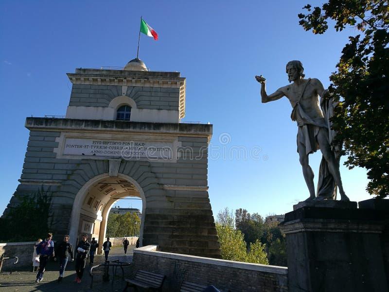 Entrance of Bridge Milvio, the oldest bridge in Rome. Italy. Entrance of Bridge Milvio, the oldest bridge in Rome, Italy. Italian flag. Statue on the right royalty free stock photography