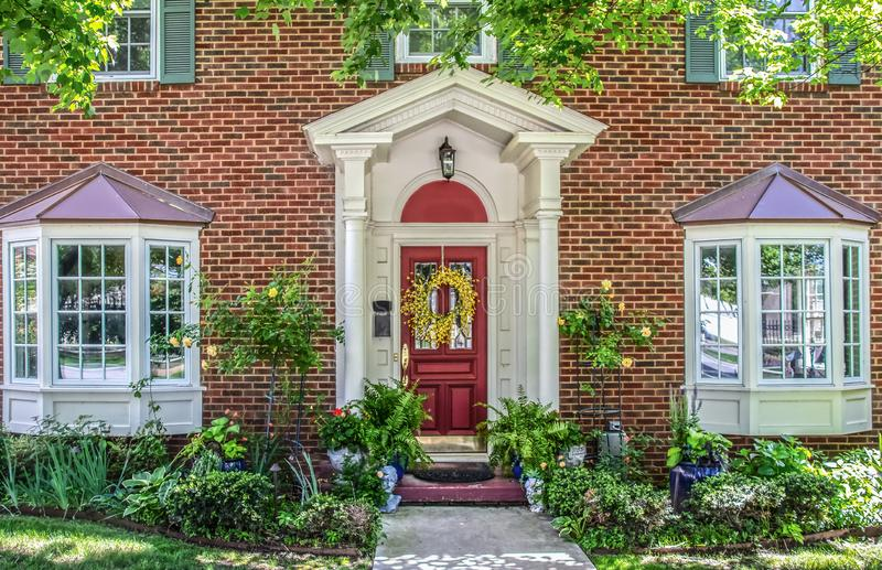 Entrance with columns and bay windows of beautiful two-story brick house with pots of flowers and yellow climbing roses and. Head planters and ferns frame by royalty free stock image