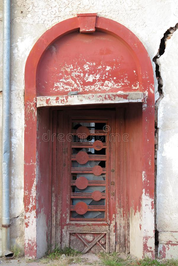 Entrance door to an old damaged building stock images