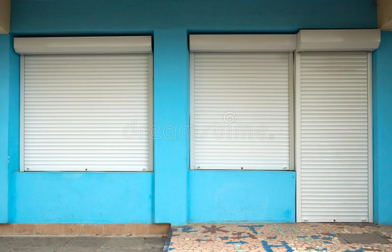 Entrance door and windows in the building, protected by roller shutters stock photography