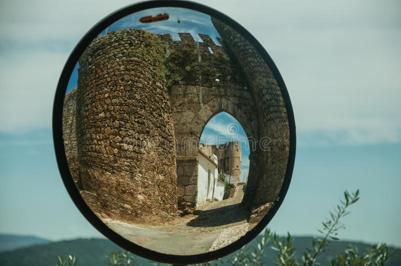 Entrance doorway reflected in street mirror at Evoramonte. Stone tower at the main entrance doorway on a sunny day, reflected in street mirror at Evoramonte. A royalty free stock images