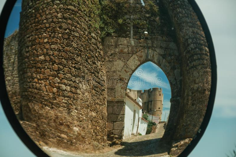 Entrance doorway reflected in street mirror at Evoramonte. Stone tower at the main entrance doorway on a sunny day, reflected in street mirror at Evoramonte. A stock photography