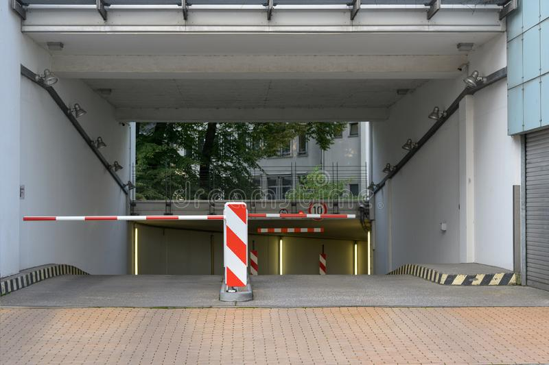 Entrance and exit driveway with barrier to a underground parking garage stock photos