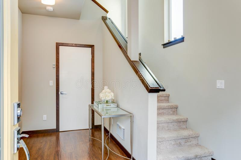 Entrance foyer with white walls and staircase. Entrance foyer with white walls, glass top console table and staircase stock image