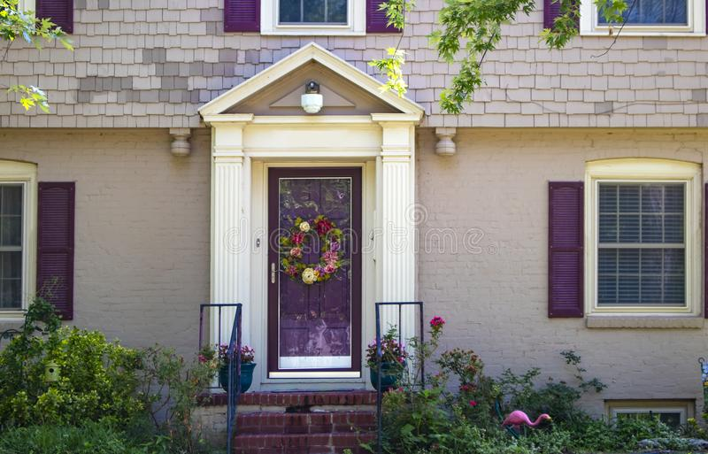 Entrance and front door of beauitufl painted brick and shingle cottage with purple shutters and triming and wreath and roses and p royalty free stock images