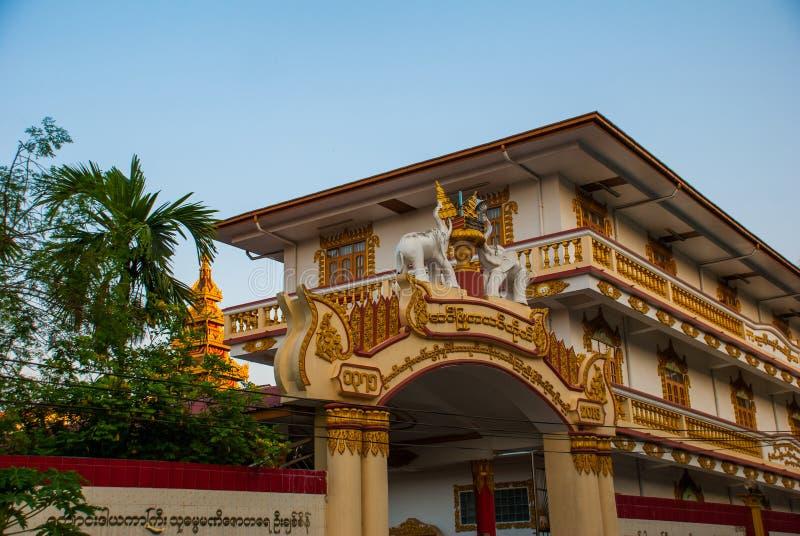 Entrance gate to the temple. Figurines of elephants. Mawlamyine. Myanmar. Burma. Beautiful temple on the street. Mawlamyine. Myanmar. Burma. Street with houses stock photos