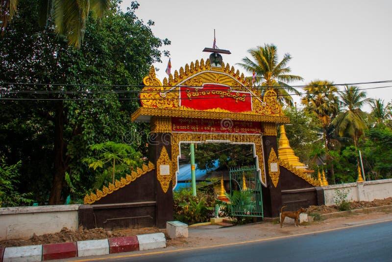 Entrance gate to the temple. Mawlamyine. Myanmar. Burma. Beautiful temple on the street. Mawlamyine. Myanmar. Burma. Street with houses stock photos