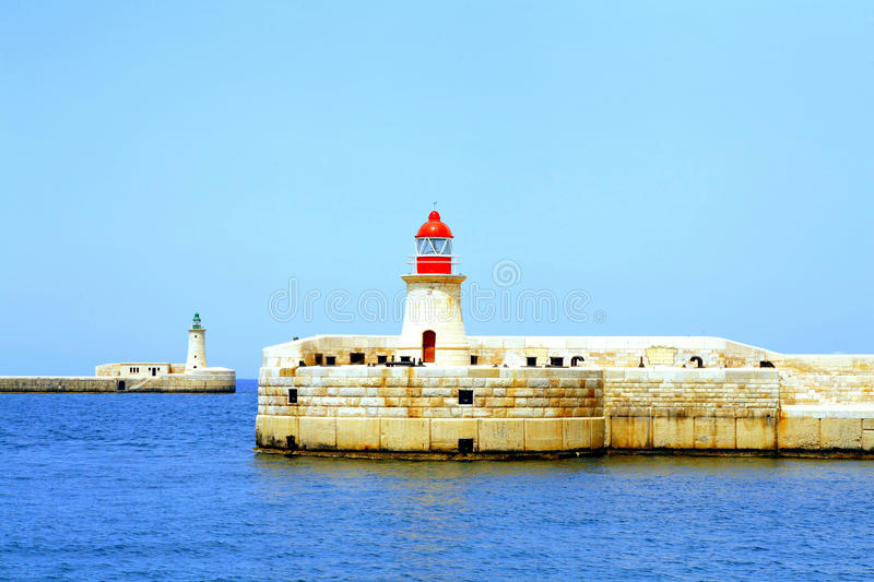 Entrance, Grand Harbour, Malta. St. Elmo and Ricasoli breakwater lighthouses at the entrance to the Grand Harbour at Malta.The lighthouses are colored green for stock photos
