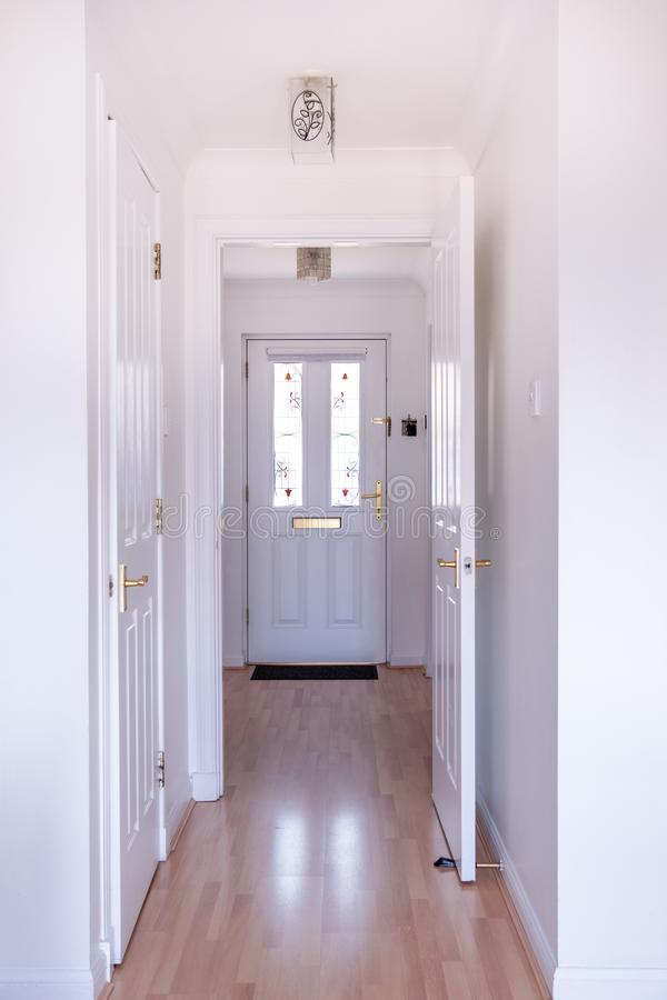 Entrance halleay to medern House with white door and stained glass inserts on door stock images
