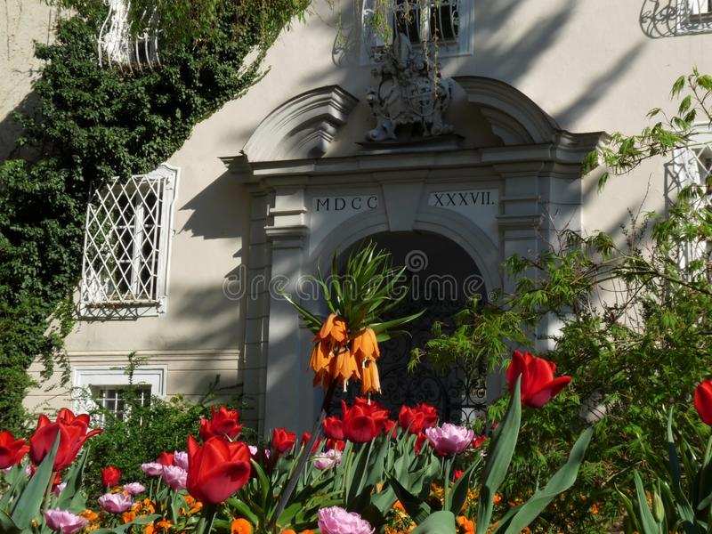 Entrance of historic monastery with flowers in front. Entrance of historic monastery at church with flowers in front royalty free stock photography