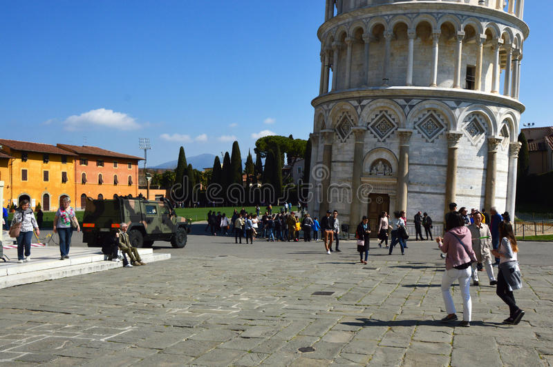 Entrance of Leaning Tower of Pisa with tourists and a military tank of italian army royalty free stock photography