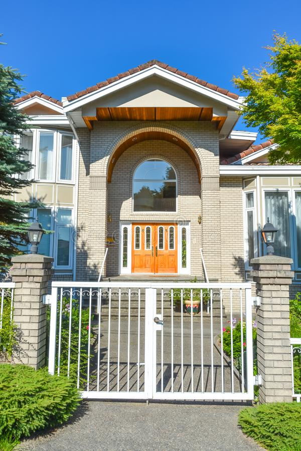Entrance of luxury family house with white gates in front. Vancouver, Canada. Entrance of luxury family house with white metal gates in front. Vancouver, Canada royalty free stock photos