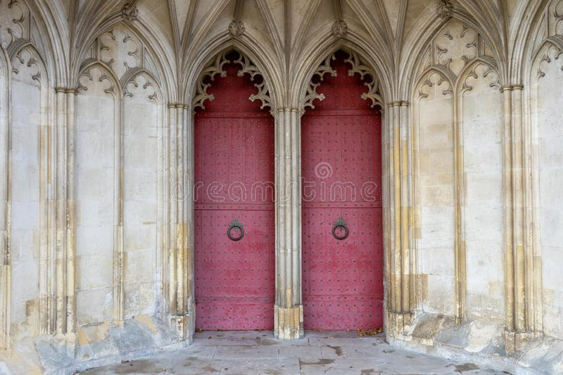 The entrance or main doors to an old English cathedral designed in the Gothic style royalty free stock photo