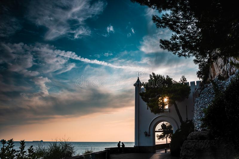 Entrance of the Miramare Castle in Trieste Italy in Europe next to the mediterranean sea with a couple while sunset. Dramatic view. Of the sky. The couple stock image