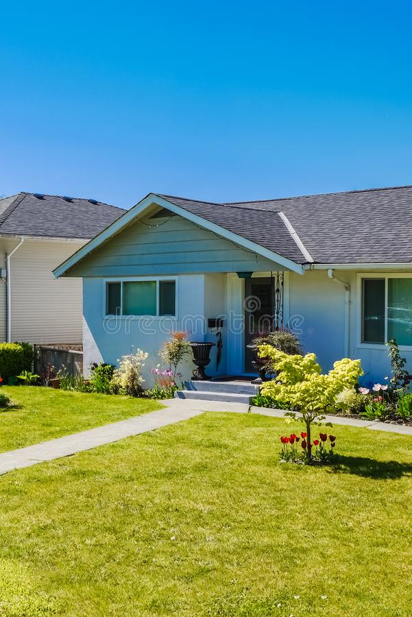 Simple residential house in North America with concrete pathway to the entrance. Entrance of modest residential house. Family house with mowed loan on the front royalty free stock images
