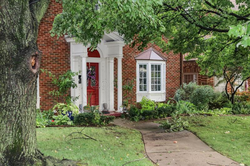 Entrance of nice brick house with bay windows after a storm that left branches and leaves littered over sidewalk and yard royalty free stock photos