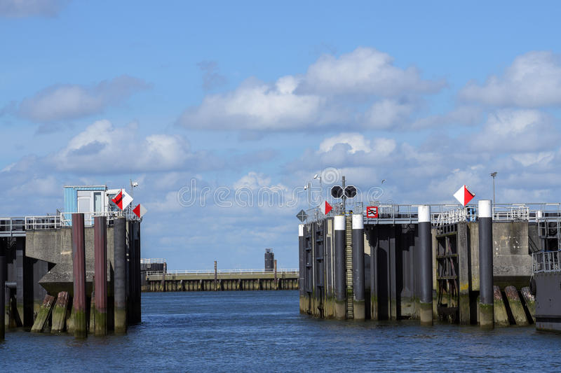 Entrance into the north sea port of cuxhaven in germany with iron gates, which can be closed at Storm surge, sunny blue sky with. Copy space royalty free stock image