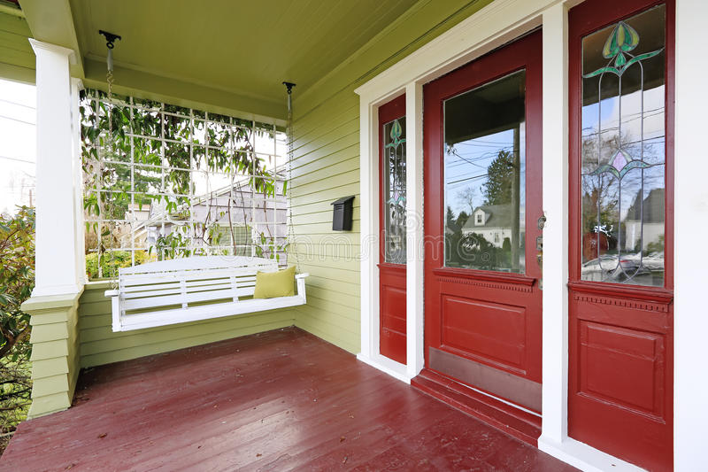 Entrance porch in red and green color with hanging swing royalty free stock photography