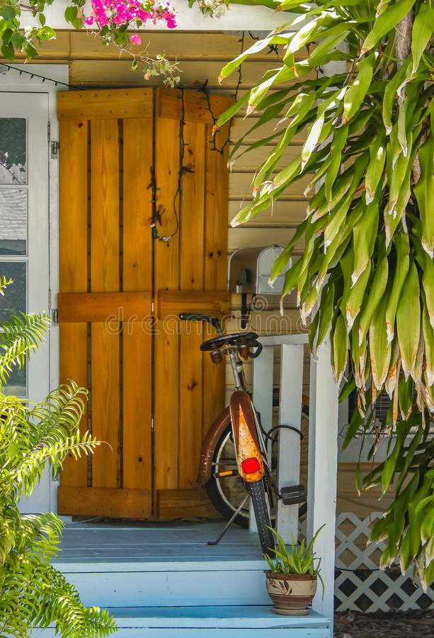Entrance and porch to Key West House with rustic hurricane shutter by door and rusted bike parked surrounded by tropical greenery. The Entrance and porch to Key stock image