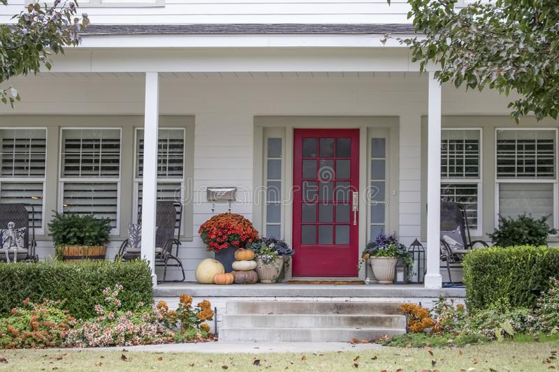 Entrance and porch to pretty house with Autumn and Halloween decorations and fall leaves blowing in the wind - curb appeal royalty free stock photography