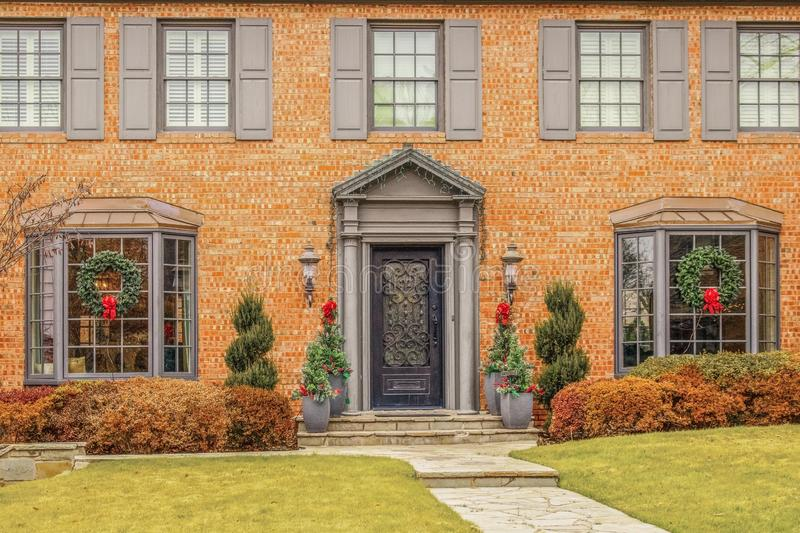Entrance of stately upscale brick home with bay windows and grayish trim decorated for Christmas stock images