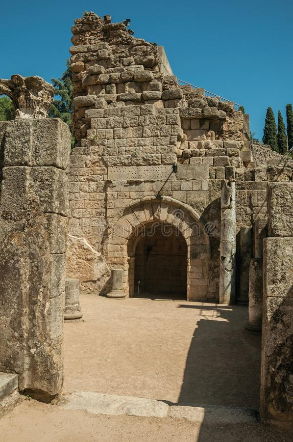 Entrance on stone wall at the Roman Theater of Merida. Arched entrance on stone wall in a sunny day at the Roman Theater, on the huge archaeological site of stock photography