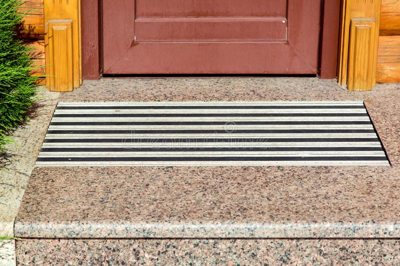 Entrance threshold with a marble step. Entrance threshold with a marble step and a rubber foot mat close-up front view royalty free stock photo