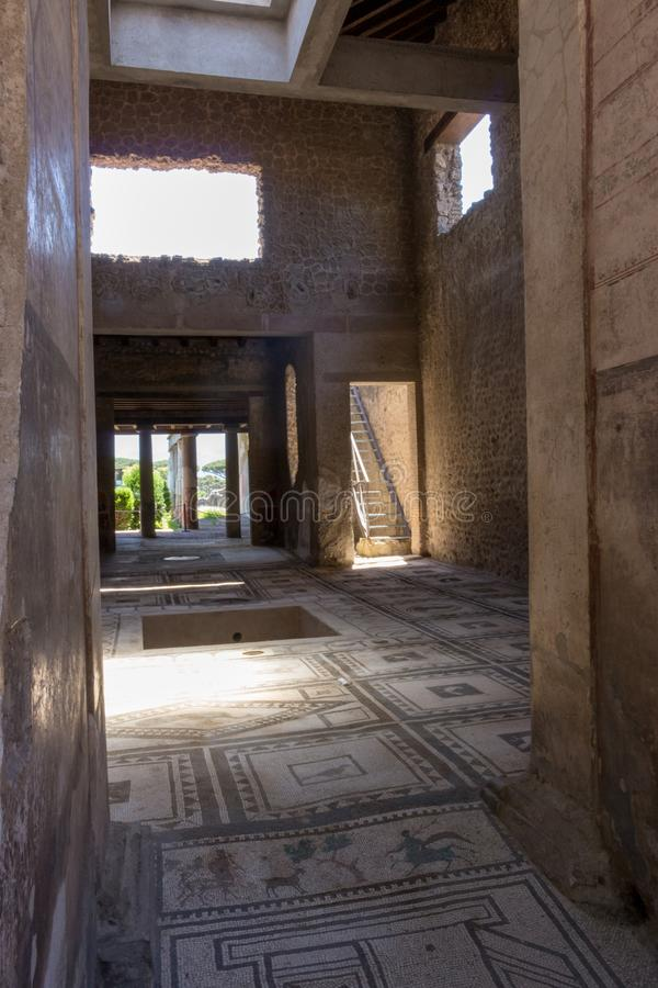 Entrance to antique roman villa in Pompeii, Italy. Ancient stone house with beautiful floor mosaic. Pompeii ruins. stock photography
