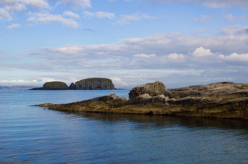 The entrance to Ballintoy harbor on the North Antrim Coast of Northern Ireland with its stone built boathouse on a day in spring. The small harbor at Ballintoy royalty free stock image