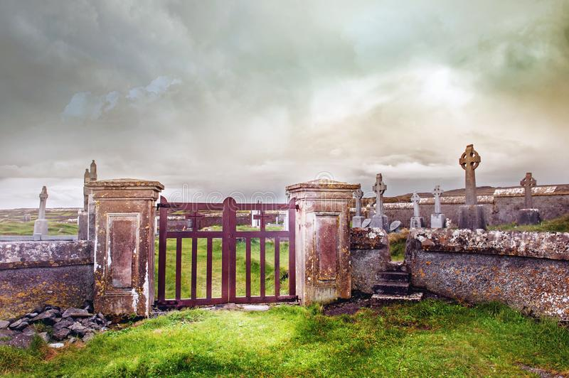Entrance to the cemetery with metal gates and concrete fence stock photo