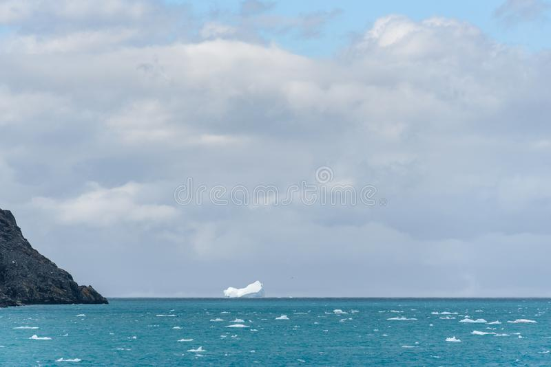 Entrance to Drygalski Fjord, South Georgia, glacier melt blue water, cloudy sky, rocky shoreline, and iceberg in background royalty free stock image