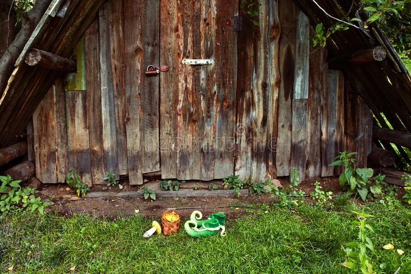 Entrance to the dwelling of a fairy forest creature, elf or dwarf, with green boots left on the doorstep with curved noses royalty free stock photo