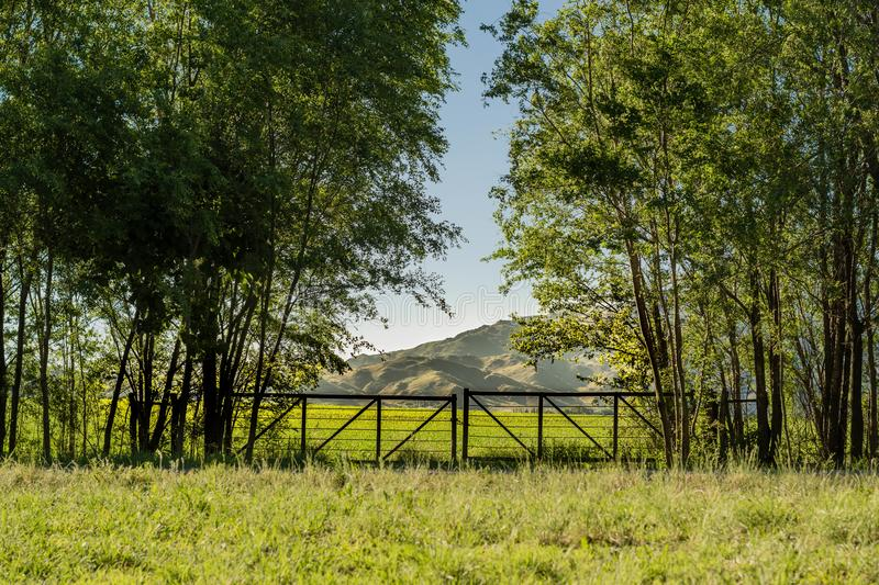 Entrance to the field with wooden gate and mountains in the background stock images