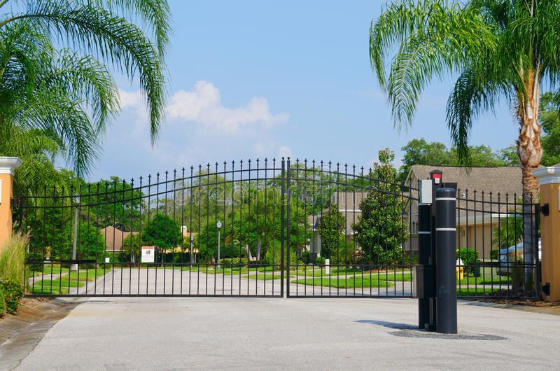 Entrance to a gated residential house community. Security entrance gate to a beautiful gated residential house community with lush green trees and grass royalty free stock photography