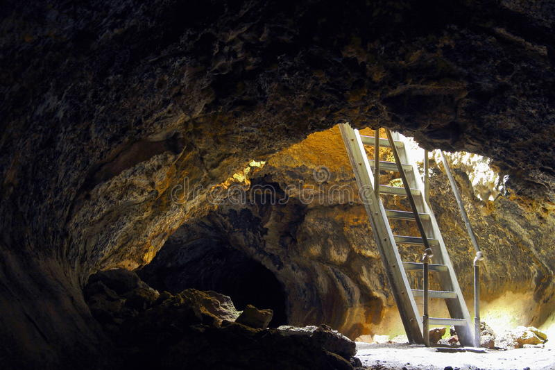 Entrance to Golden Dome Cave, Lava Beds National Monument near Klamath Falls, California. Ladder leading into Golden Dome Cave, one of the larger lava tube caves stock image