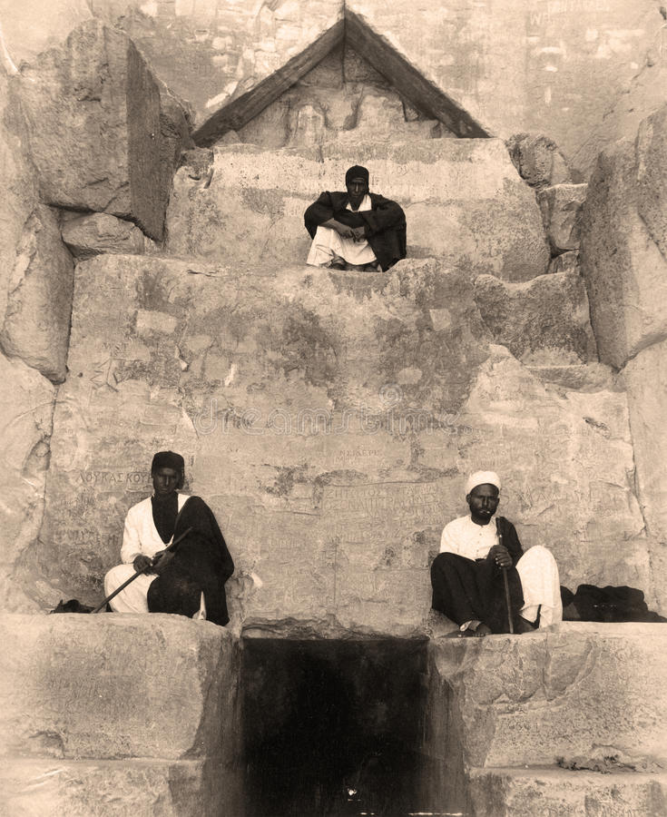 The Entrance to the great pyramid of Giza 1880. The Entrance to the great pyramid. The three Egyptian men sitting at the entrance. This photo was taken during royalty free stock images