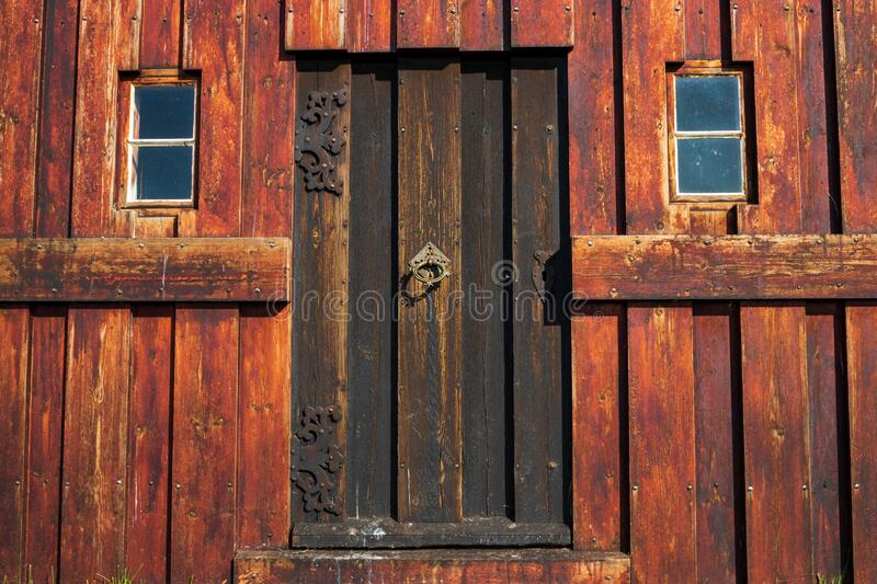 Entrance To Grungy Old Wooden Building With Two Windows And Antique Door Handle stock photos