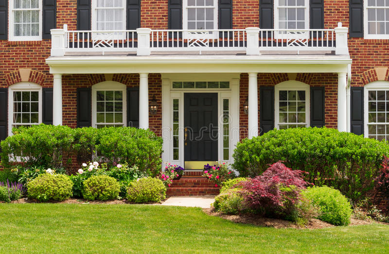 Entrance to large single family home. Entrance doorway to large single family modern US house with landscaped gardens and lawn on a warm sunny summers day stock photography