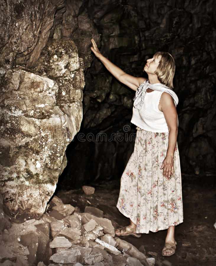 At the entrance to the mountain cave. An elderly tourist at the entrance to a mountain cave royalty free stock photos