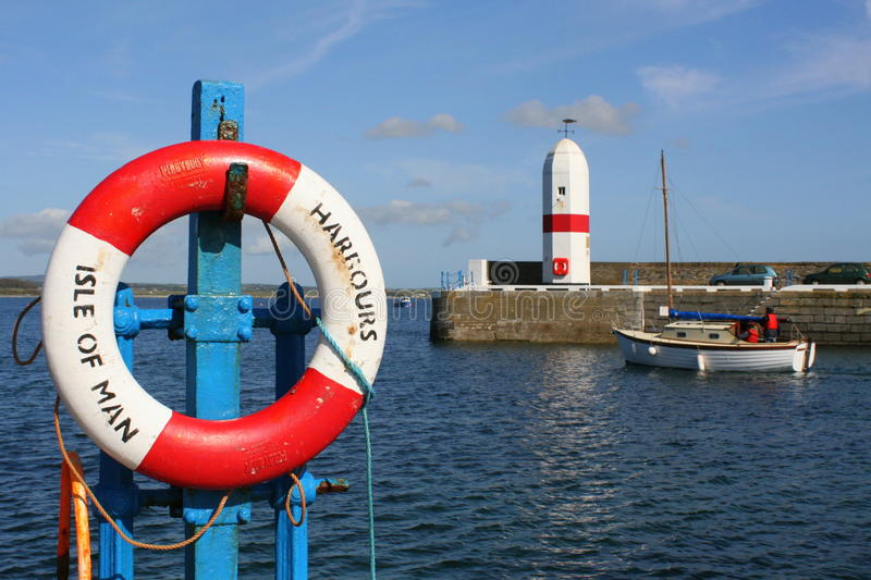 Harbour light and lifebelt. Entrance to Port St. Mary, Isle of Man royalty free stock photos