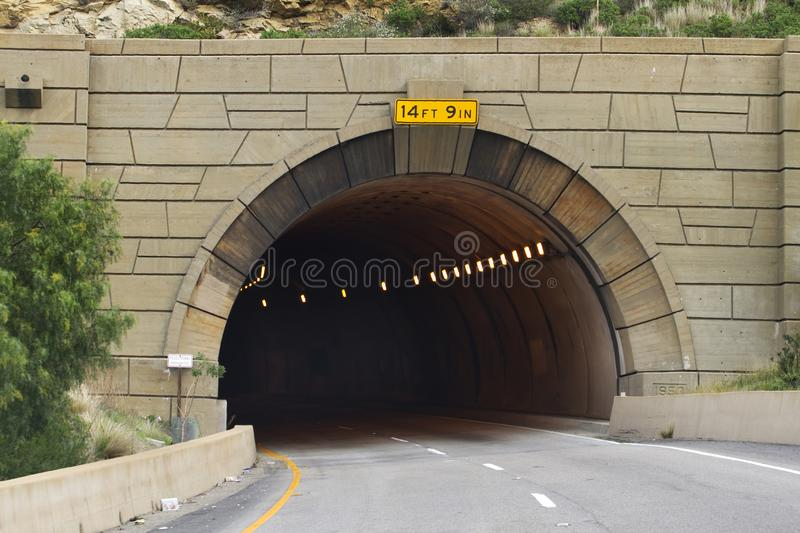 Entrance to a tunnel into the Dark. A Southern California road going under a rocky mountain. There are no cars just lights leading into the darkness royalty free stock images