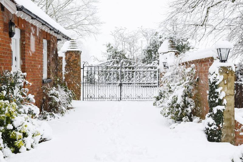 Driveway to rural house in snow. Entrance to Victorian house with cast iron gates with driveway covered in snow in winter royalty free stock photography
